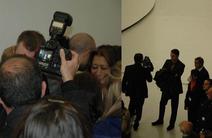 (L) Zaha enjoys a moment in the spotlight (R) A cameraman obliviously passes Patrik Schumacher as he stands in the wings